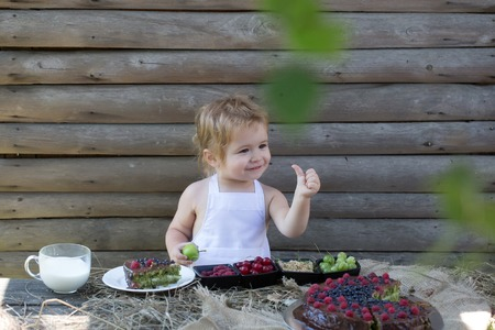 pinafore: Cute little boy with blond hair in white pinafore gives thumb up hand gesture sign of approval at table with fruit cake berries and milk on wooden background