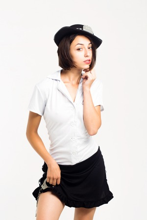 uniform skirt: Young woman brunette with pretty sexy face in police uniform white t shirt black cap and skirt posing showing legs holding iron wristbands isolated