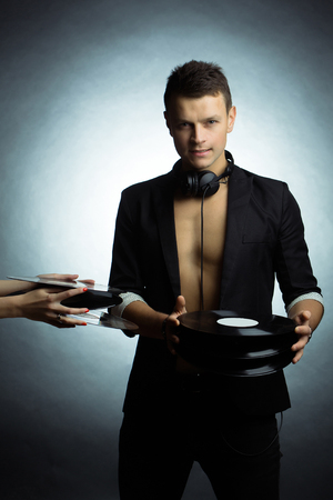 dj boy: Young boy music dj with handsome face in black suit and bare chest holding many vinyl records and female hands give him discs on white background studio