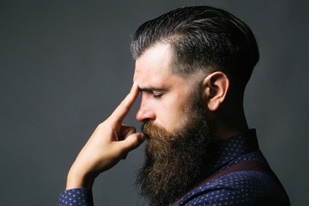 Handsome man businessman stylish hipster with long beard and moustache thinks with closed eyes on gray background