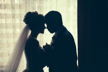 african american woman silhouette: Silhouette of bride beautiful young woman and groom handsome african American man share love head to head on background of window