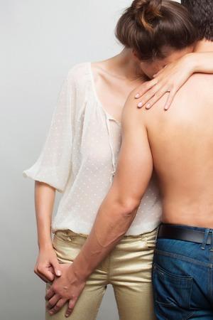 筋肉男の背中ときれいな女性や灰色の背景のスタジオで白のブラウスで ...