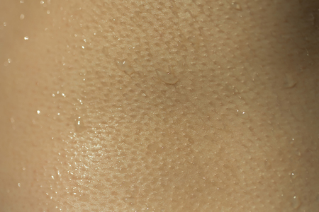 suncare: Wet skin human texture with water drops closeup background