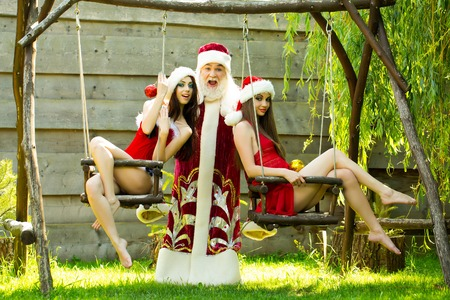 Funny santa claus man in new year Christmas red costume with pretty girls in sexy dresses on swing on natural background