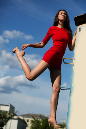 young sexy fashionable woman or girl with long brunette hair and pretty face in stylish red dress on slim body and shoes on high heels climbing on house stairs on blue sky background outdoor Stock Photo