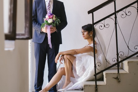 elegant staircase: Beautiful bride woman with sexy legs in white wedding dress and veil sits on staircase near elegant groom man with bouquet Stock Photo