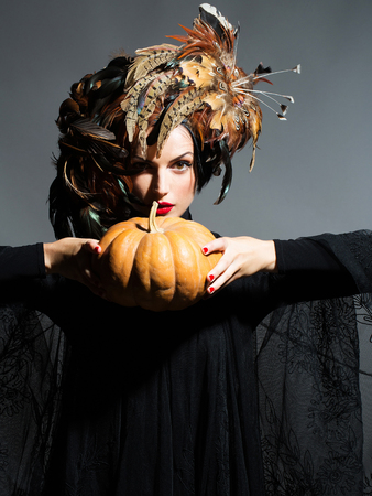 young sexy woman or girl with red lips on pretty face in beautiful feather hat brown color holds halloween pumpkin in black costume on grey background Stock Photo
