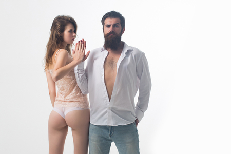 couple of handsome bearded man with long beard and moustache on serious face near young pretty girl with sexy body and buttocks in lingerie in studio isolated on white background, copy space