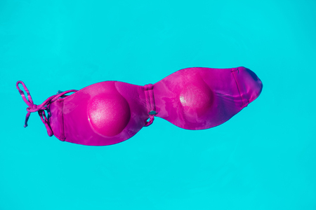brassiere: wet female swimsuit bra or brassiere pink color floating in blue water of swimming pool with nobody Stock Photo