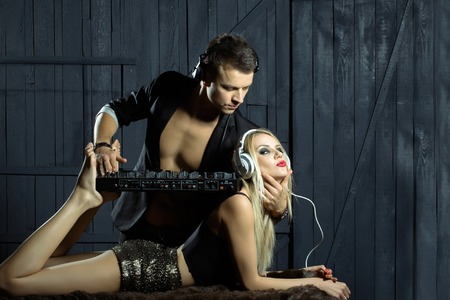 dj boy: Young boy musician with handsome face with headset in black suit playing music on electronic dj mixer standing on shoulders and legs of sexy woman blonde in glamour shorts barefoot studio