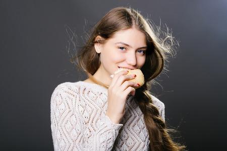 comiendo pan: chica de moda atractiva o una mujer con la cara muy sonriente modelo delgado con estilo de pelo largo Morena en pan de rollo suéter blanco que come en el estudio sobre fondo gris