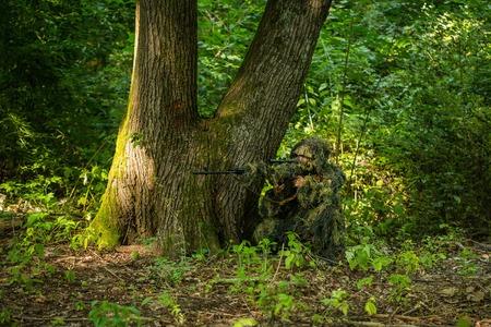 Sniper man in militair ghilliekostuum camouflage met geweer in handen gericht doelwit zitten in hinderlaag in de buurt van boom in het bos Stockfoto