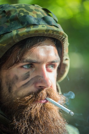 aggressiveness: Soldier man with tied and grime bearded face in military helmet and ammunition smoking cigarette outdoor closeup Stock Photo