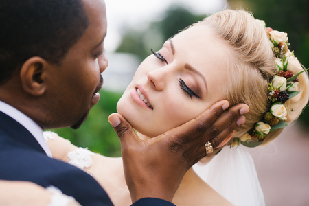 gently: Loving groom african American man gently touches face of beautiful bride blond woman with elegant hairstyle and wreath outdoors on wedding day Stock Photo