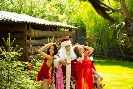 peignoir: Man in santa red costume with sexy women looking at negligees near fir on wooden building background outdoor Stock Photo