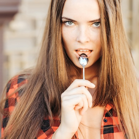 tea spoon: young pretty girl or woman with long hair in red checkered shirt holding metallized tea spoon outdoor Stock Photo