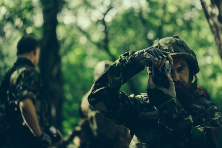 Young soldier man with beard on grime serious face in ammunition and helmet holding camera in his hands on background of soldiers in forest