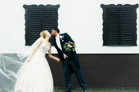married couples: Beautiful bride woman in long elegant white lace dress veil and groom african American man just married couple kiss on wedding day