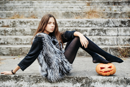 young halloween sexy woman or girl witch with long hair and pretty face in black tights and fur waistcoat sit on stony stairs with traditional autumn holiday symbol of orange spooky pumpkin outdoor