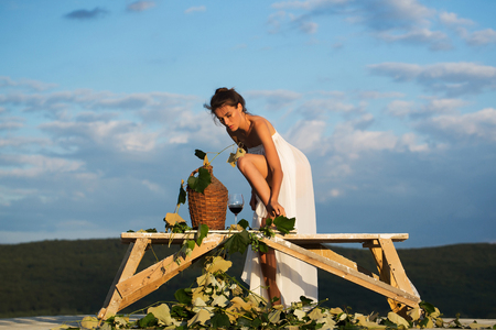 Beautiful girl in white sexy dress denuded with red wine in glass wicker bottle vine and grapes on nature over blue sky Stock Photo