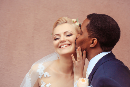 tenderly: Young man african American groom kisses tenderly beautiful woman happy bride on wedding day