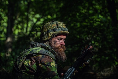 aggressiveness: Young soldier with sad bearded face in military helmet and camouflage with gun on forest background