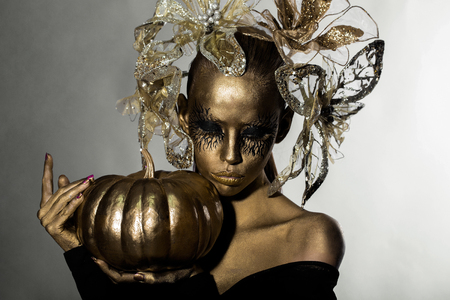 body paint sexy: halloween golden woman or girl holding painted gold pumpkin has pretty face with makeup and body art metallized color with decorative flowers on head on white grey background