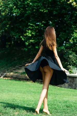 Attractive young girl with long dark hair and navy blowing up dress jumps on the lawn looks away