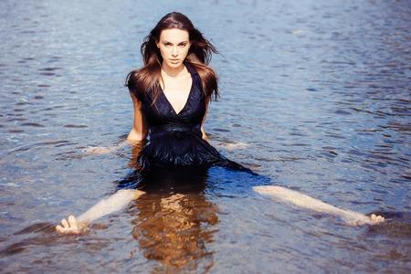 beine spreizen: Sexy junges Mädchen in navy Kleid mit langen dunklen Haaren sitzt im Wasser mit gespreizten Beinen