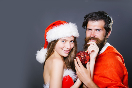 costume ball: Young woman with smile on pretty face in christmas red and white costume and hat with bearded handsome smiling new year man hipster in santa claus suit holding decorative ball studio copy space Stock Photo