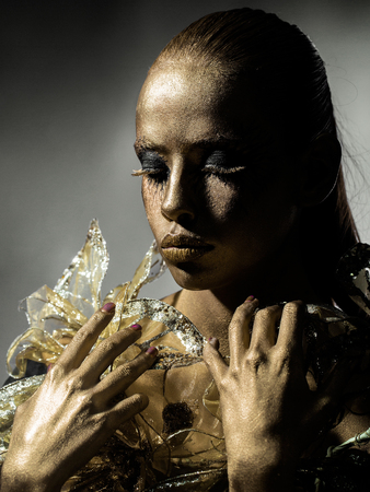 metallized: golden woman or girl has pretty face with makeup and body art metallized color with decorative flowers on grey background Stock Photo