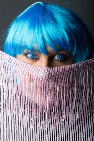Man with blue eyes in fashionable short wig behind lilac scarf on grey background