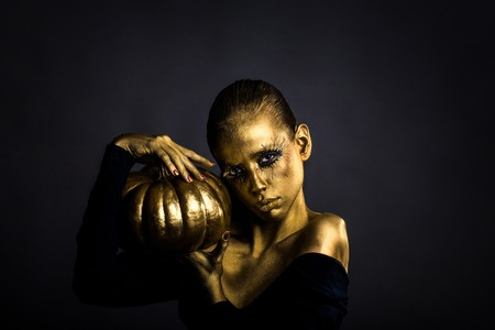 metallized: halloween golden woman or girl holding painted gold pumpkin has pretty face with makeup and body art metallized color with bare shoulders on grey background