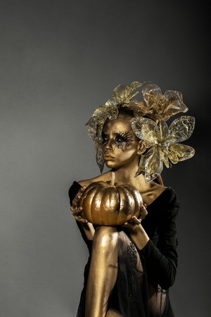 cinderella pumpkin: halloween golden woman or girl holding painted gold pumpkin has pretty face with makeup and body art metallized color with decorative flowers on head on grey background Stock Photo