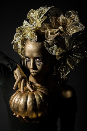 cinderella pumpkin: halloween golden woman or girl holding painted gold pumpkin has pretty face with makeup and body art metallized color with decorative flowers on head on black background