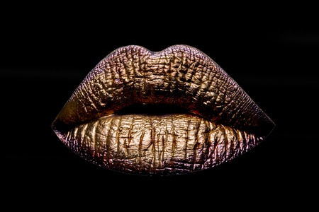 female golden or gold lips isolated on black background as makeup or body art painted mouth metallized color with violet contour