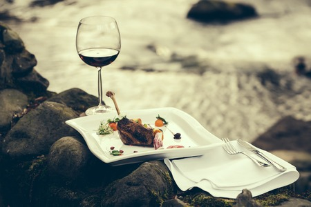 bocal: Picnic near water, decorated meat with lemon, glass of wine, served food