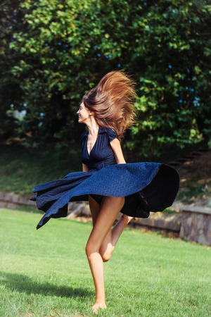sexy girl dance: Attractive sexy happy young girl with long hair and navy dress jumps on the lawn