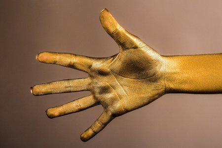 metallized: female golden or gold hand or arm with palm and fingers with body art painted metallized color on grey background, closeup