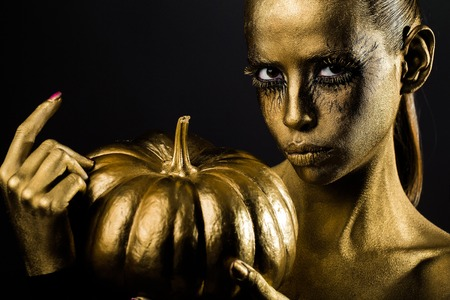 halloween golden woman or girl holding painted gold pumpkin has pretty face with makeup and body art metallized color on black background Reklamní fotografie