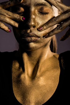 metallized: golden woman or girl has pretty face with makeup and body art metallized color holding hands and fingers near head, closeup Stock Photo