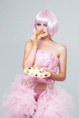 paletas de caramelo: sexy glamour girl or woman with fashionable makeup on pretty face and short hairstyle or pink wig in dress eating colorful marmalade sweets on paint palette in studio on grey background Foto de archivo