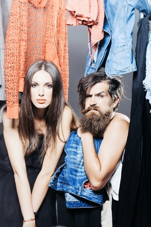 Fashion couple denuded of brunette girl and bearded man choose clothes to wear near rack in wardrobe closet Stock Photo