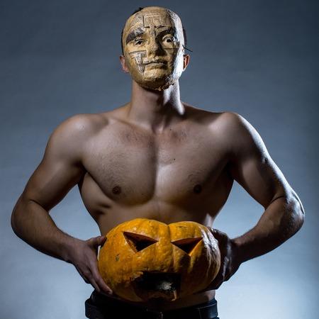 nackte brust: Junger stattlicher Mann in der Maske der Zeitung mit muskulösen Körper nackte Brust und Rumpf posiert im Studio auf grauem Hintergrund gelb Halloween-Kürbis halten