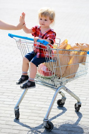 baby sit: Cute baby boy blond child in plaid shirt sits in shopping trolley and eats cookie from paper packet outdoors on sunny day