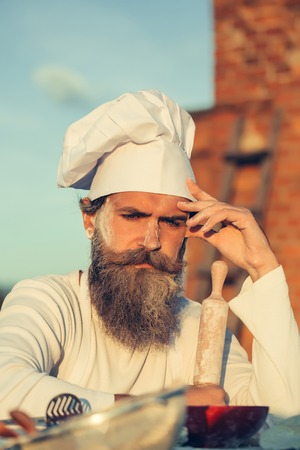 leaned: Handsome bearded man cook chef with flour on face and white hat with long beard thinking leaned on table on stony wall with ladder on background Stock Photo