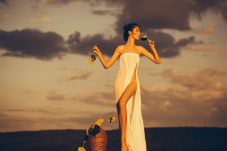 Pretty young girl or woman in white sexy dress denuded with red wine in glass wicker bottle vine and grapes on nature over sky in sunset Stock Photo