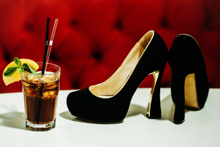 lady's: Black ladys shoes and nonalcoholic cocktail with lemon and mint in glass with transparent and black rolls on white table on red background Stock Photo