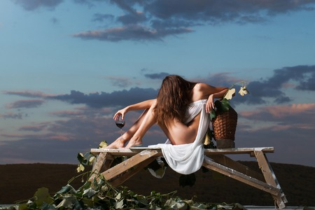 denuded: pretty girl in white sexy dress denuded gorgeous body with red wine glass wicker bottle and vine on evening nature over dramatic sky Stock Photo