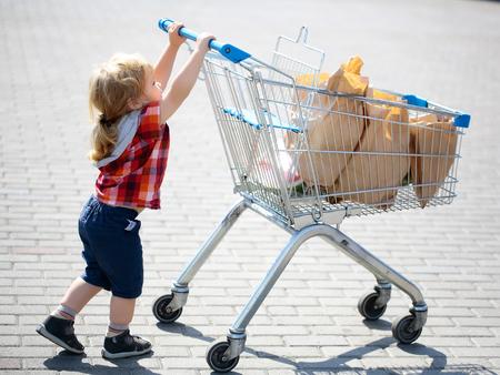 niño empujando: Bebé lindo niño rubio en camisa de cuadros empujando carrito de la compra con el paquete de papel al aire libre en un día soleado